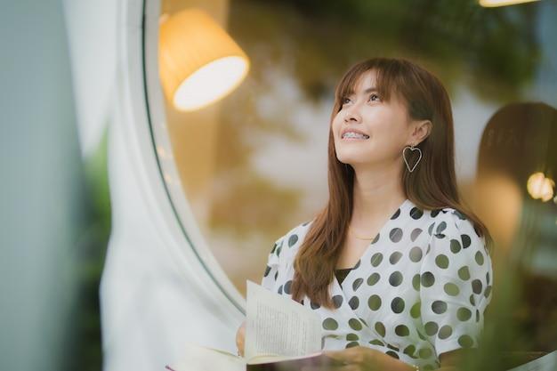 Mulher asiática lendo livro com felicidade no tempo livre
