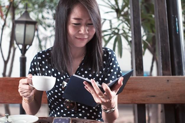 Mulher asiática lendo livro e beber café ou chá com feliz