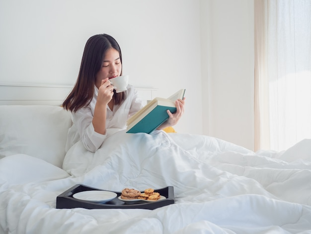 Mulher asiática lendo livro e tomando café na cama de manhã