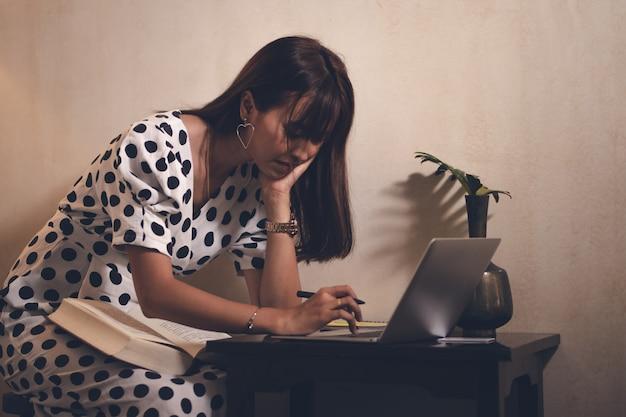Mulher asiática lendo livro e usando o laptop, bloco de notas no tempo livre com feliz