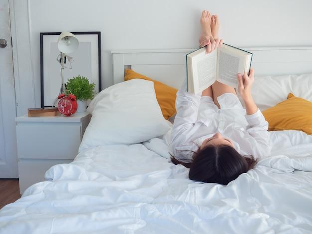 Mulher asiática lendo livro na cama de manhã