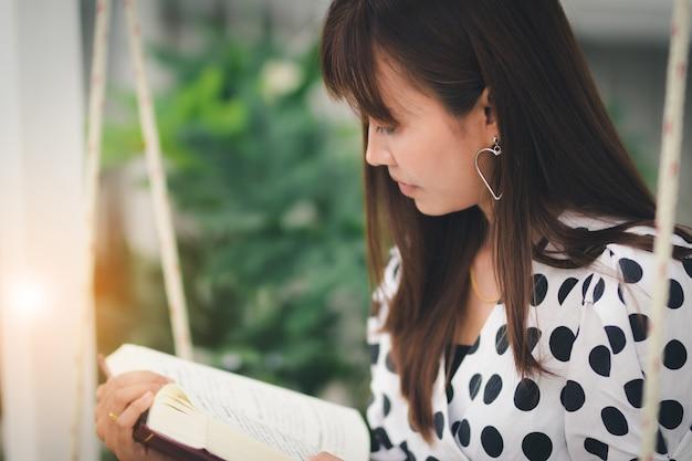 Mulher asiática lendo livro no tempo livre com feliz