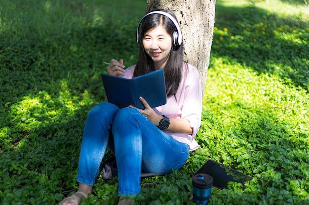 Mulher asiática lendo um livro e sorrindo no parque mulher asiática satisfeita lendo um livro em um parque
