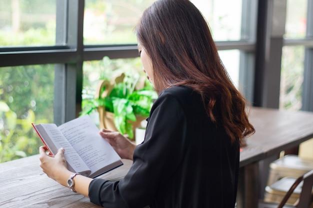 Mulher asiática lendo um livro para o tempo de relaxamento