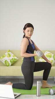 Mulher asiática levantando barra com meio braço enquanto se agacha em casa