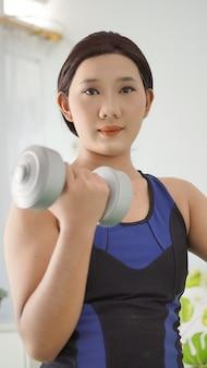 Mulher asiática levantando barra de braço completo em casa
