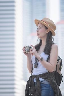Mulher asiática linda turista solo desfrutar de tirar foto pela câmera retro