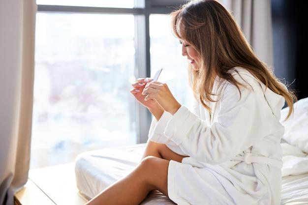 Mulher asiática lixa as unhas com uma lixa enquanto está sentada na cama de roupão de banho em casa, cuida de si mesma, conceito de beleza.
