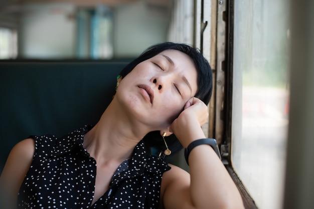 Mulher asiática madura dormindo no vagão do trem