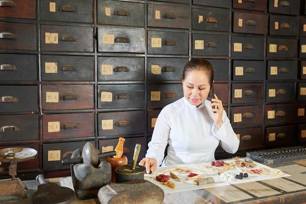 Mulher asiática madura embalando pedidos em boticário