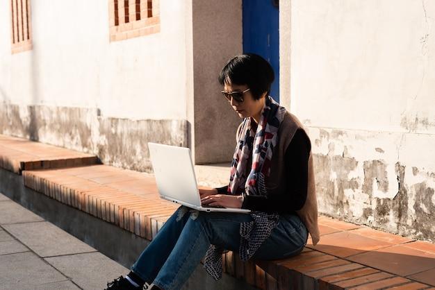 Mulher asiática madura senta-se na escada e usa o laptop nas antigas construções chinesas