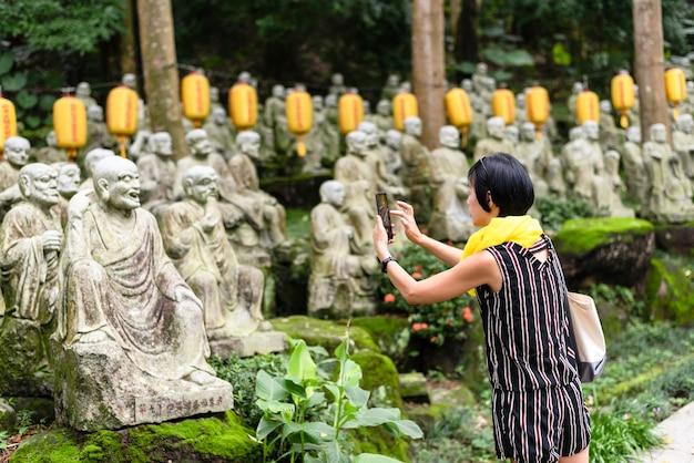 Mulher asiática madura tira uma foto em um jardim com estátuas de pedra arhat