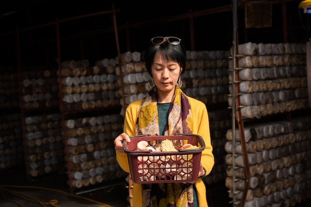 Mulher asiática madura viaja e visita uma fazenda de cogumelos no município de puli, taiwan