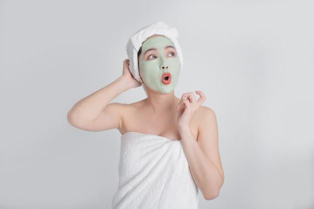Mulher asiática máscaras de rosto de creme verde sobre fundo branco. ela ficou feliz e surpresa.