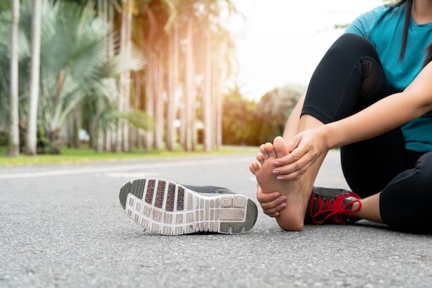 Mulher asiática massageando seu pé doloroso durante o exercício