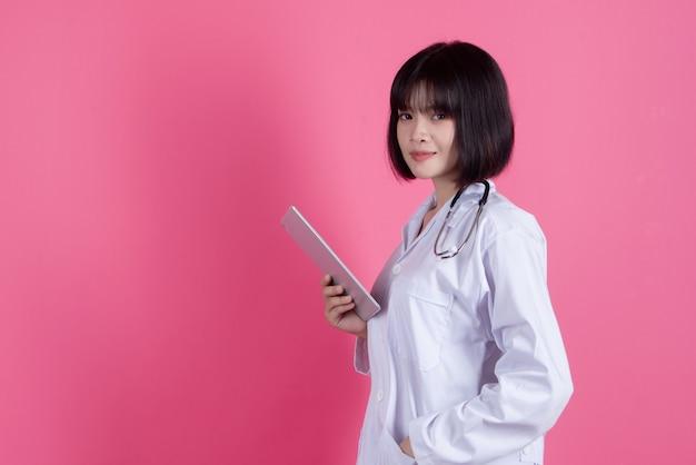 Mulher asiática médico com jaleco branco sobre rosa