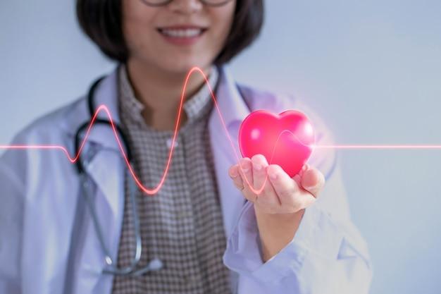 Mulher asiática médico usando óculos segure seu coração sorrindo amigável.