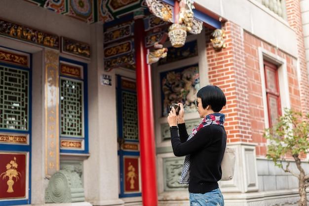 Mulher asiática moderna segurando uma câmera viajando em um antigo prédio chinês