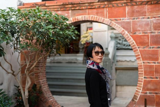 Mulher asiática moderna viajando em um antigo prédio chinês
