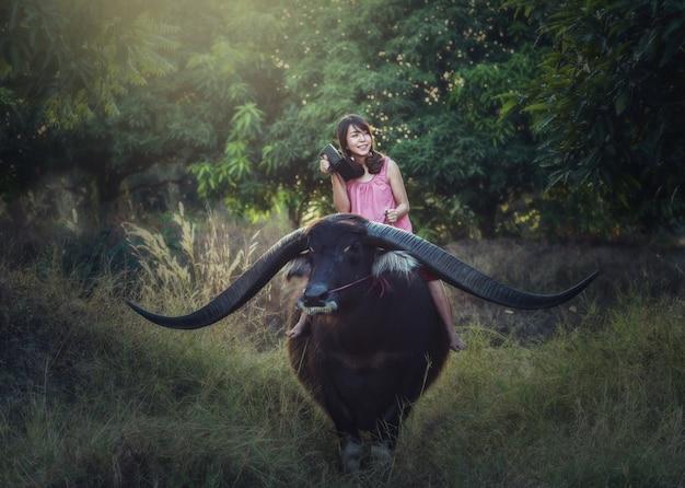 Mulher asiática, montando, búfalo, com, rádio