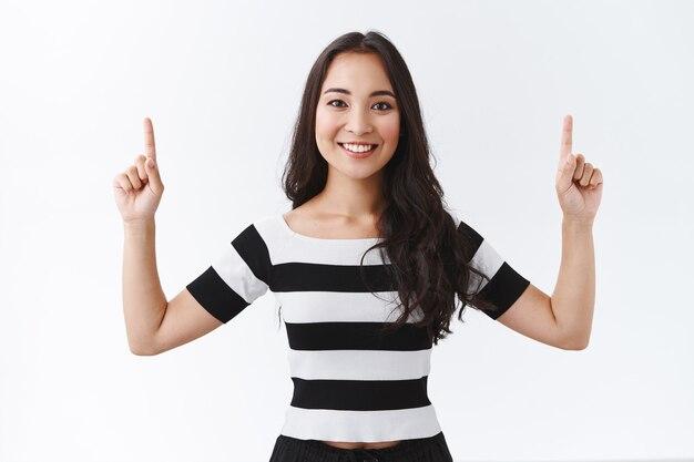 Mulher asiática morena bonita e entusiasmada com uma camiseta listrada, levantando os dedos e apontando para cima com uma expressão alegre e feliz, apontando o anúncio superior, sorrindo alegre, fundo branco