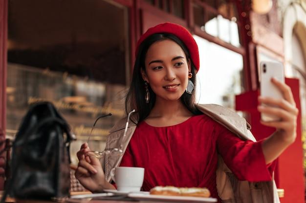 Mulher asiática morena de olhos castanhos em uma boina estilosa, vestido vermelho, sobretudo bege, sentada em um aconchegante café de rua, segura óculos da moda e tira selfie