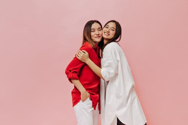 Mulher asiática morena em uma camisa longa e grande e uma garota alegre de cabelos curtos em uma blusa vermelha e calça branca se abraçam na parede rosa