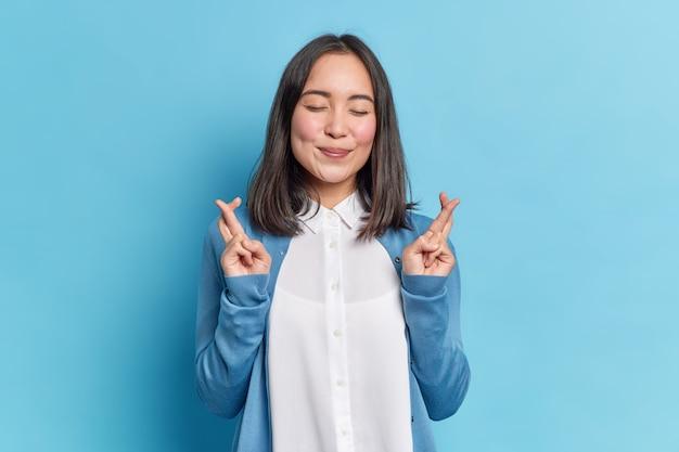 Mulher asiática morena feliz e esperançosa cruza os dedos de boa sorte reza para que os sonhos se tornem realidade estando bem vestida fecha os olhos