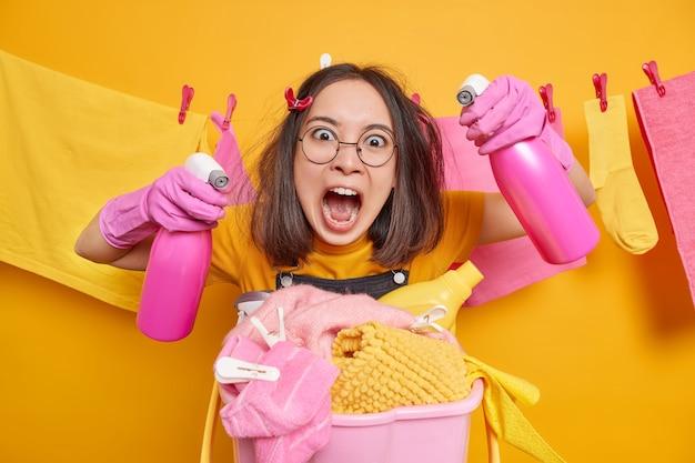 Mulher asiática morena furiosa gritando de raiva segurando dois frascos de spray prontos para limpar poses de apartamento perto do cesto de roupa suja usa óculos redondos, luvas de borracha, varal com roupas lavadas atrás
