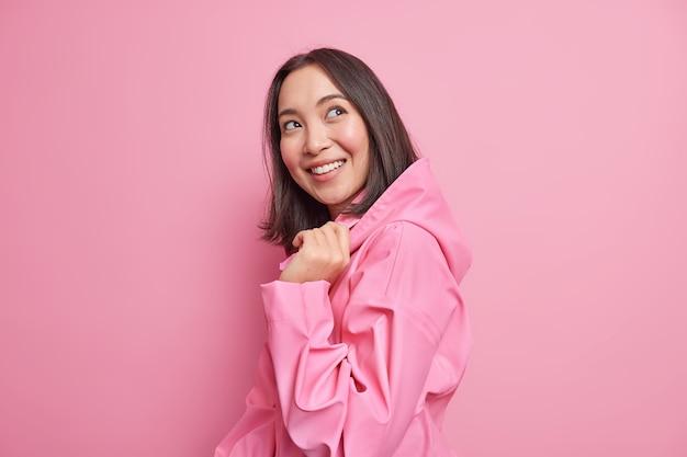 Mulher asiática morena muito feliz fica meio virada contra a parede rosa tem bom humor usa jaqueta elegante com capuz pensa em algo agradável poses feliz interior. conceito de emoções