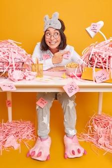Mulher asiática morena otimista positiva em roupa de dormir trabalha na mesa do escritório cercada por pontas de papel cortadas e come deliciosos flocos de milho isolados sobre a parede amarela
