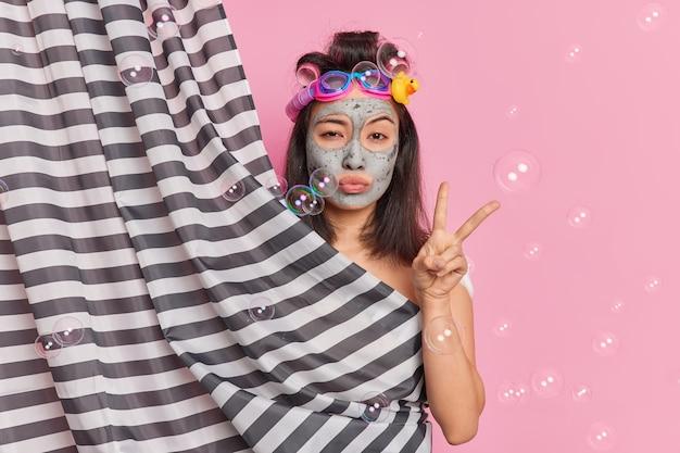 Mulher asiática morena séria faz gesto de paz escondendo corpo nu atrás de poses de cortina de chuveiro em ducha aplica máscara de argila para refrescar a pele