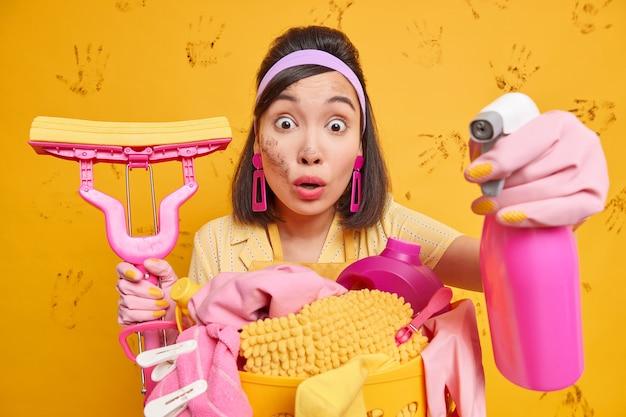 Mulher asiática morena surpresa com os olhos arregalados para a câmera usando detergente de limpeza e o esfregão limpa a poeira traz a casa em ordem poses contra a parede amarela suja