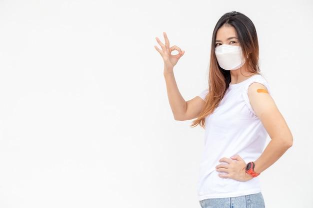 Mulher asiática mostra bandagem no braço mulher asiática feliz se sente bem depois de receber a vacina