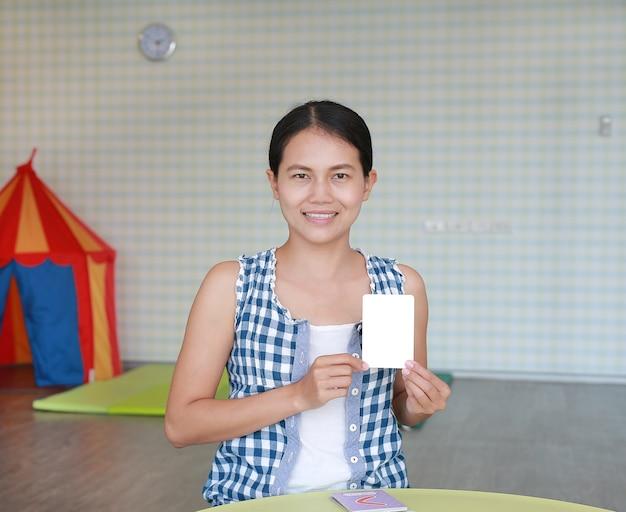 Mulher asiática mostra o cartão flash em branco para o desenvolvimento do cérebro direito na sala de jogos kid