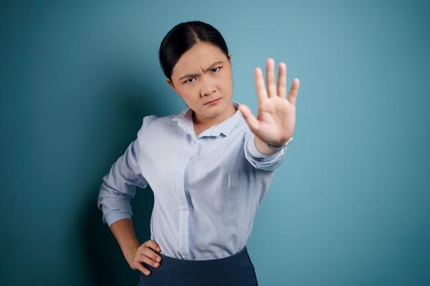 Mulher asiática mostrando a mão que faz o sinal de pare em pé isolado em azul.