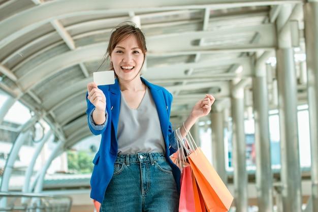 Mulher asiática mostrando cartão de crédito. pagamento online e conceito de compras.