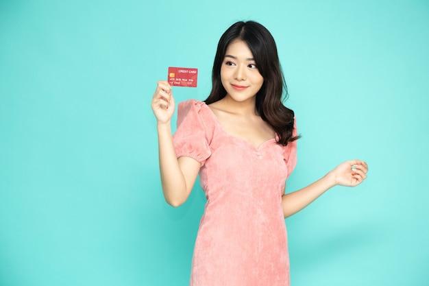 Mulher asiática mostrando cartão de crédito para fazer pagamento ou pagar negócios online.