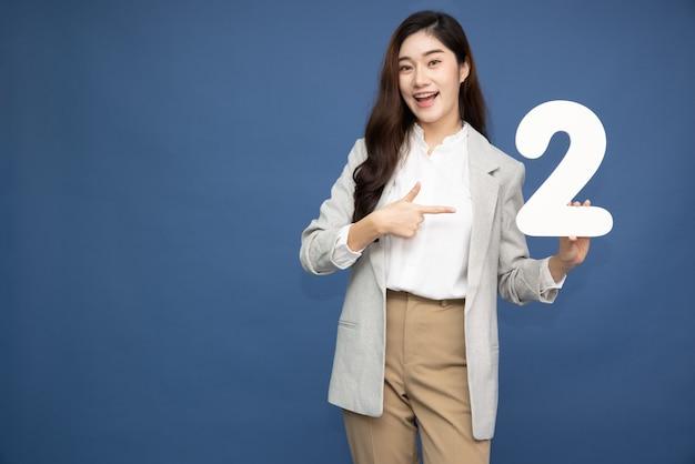 Mulher asiática mostrando o número 2 e apontando para cima com o dedo isolado no fundo azul