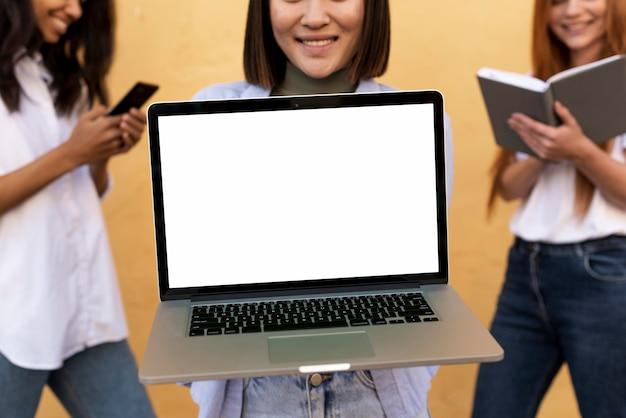 Mulher asiática mostrando um laptop vazio