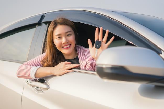 Mulher asiática motorista sorrindo e mostrando a chave do carro novo enquanto está sentado em um carro