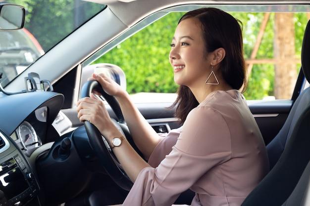 Mulher asiática motorista sorrindo e sentada dentro do carro enquanto o trânsito fica engarrafado na estrada