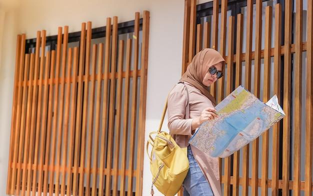 Mulher asiática muçulmana de viajante olhar e segurar no mapa de mãos