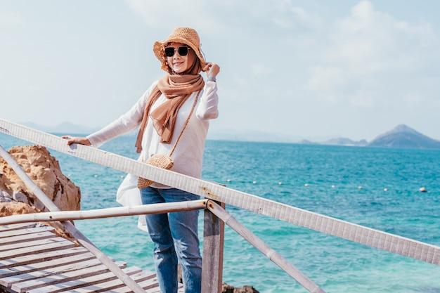 Mulher asiática muçulmana nova feliz que olha da ponte de madeira.