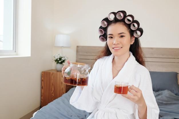 Mulher asiática muito jovem e alegre com rolos de cabelo na cabeça, bebendo chá de ervas depois de tomar banho