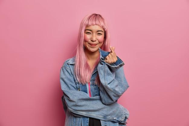 Mulher asiática muito romântica com sorriso fofo de amor, cabelo rosa comprido, faz sinal do dedo do coração coreano, expressa amor e simpatia, confissão