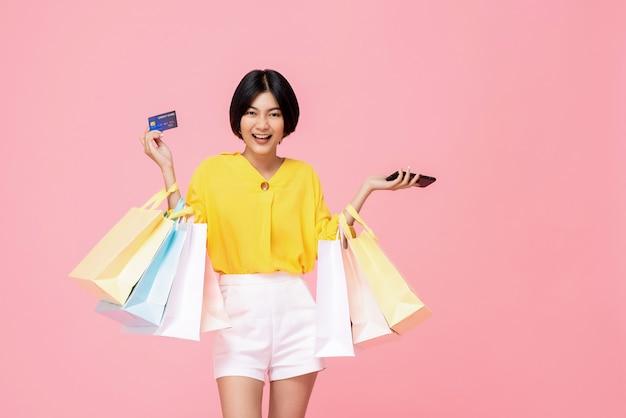 Mulher asiática muito sorridente com sacos de compras, mostrando o cartão de crédito