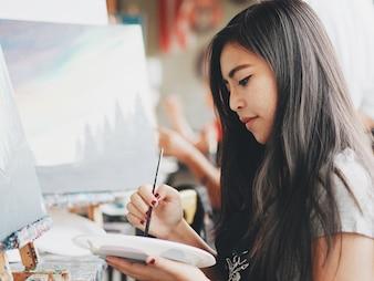 Mulher asiática na aula de pintura