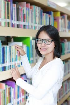 Mulher asiática na biblioteca, selecionando o livro para ler