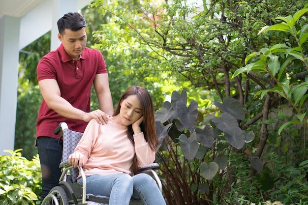 Mulher asiática na cadeira de rodas e infeliz e dolorosa.